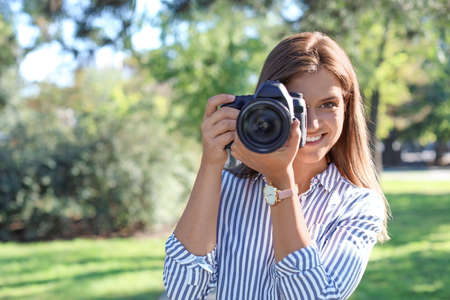 Young female photographer with professional camera in park. Space for text Zdjęcie Seryjne