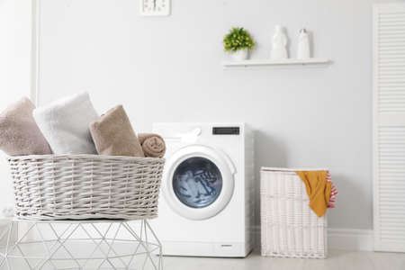 Basket with laundry and washing machine on background. Space for text