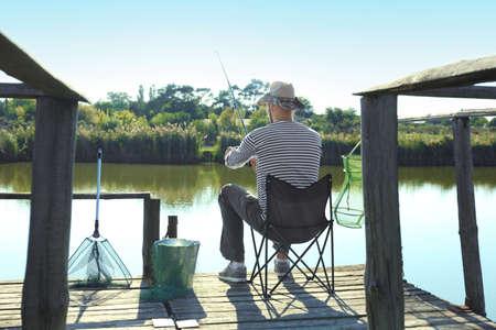 Young man fishing alone on sunny day 版權商用圖片