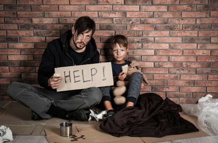 Poor man with his son asking for help near brick wall