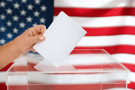 Elderly woman putting ballot paper into box and American flag on background, closeup Stock Photo