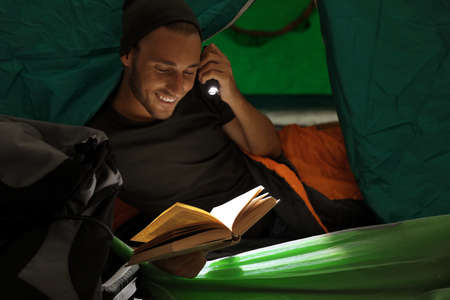 Young man in sleeping bag reading book with flashlight inside of tent
