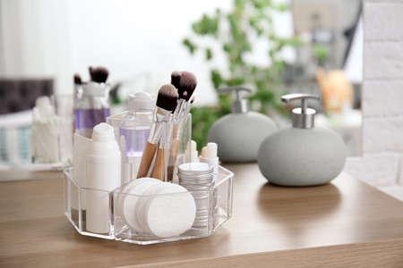 Organizador con productos cosméticos en la mesa de madera en el baño. Foto de archivo