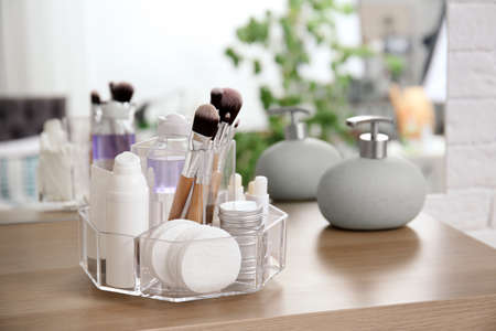 Organizer with cosmetic products on wooden table in bathroom Foto de archivo