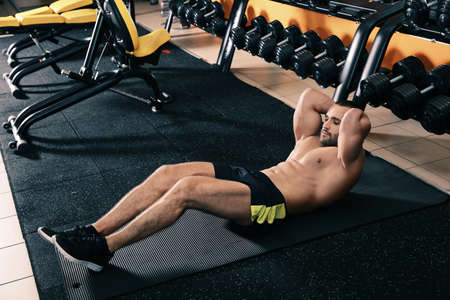 Strong man doing crunches on mat in gym