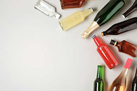 Flaschen mit verschiedenen alkoholischen Getränken auf hellem Hintergrund, Draufsicht. Platz für Text Standard-Bild
