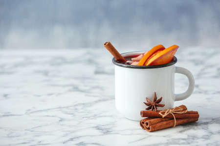 Mug with red mulled wine on marble table. Space for text