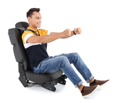 Young man sitting in car seat with safety belt on white background