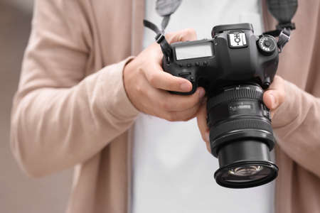 Male photographer with professional camera, closeup view