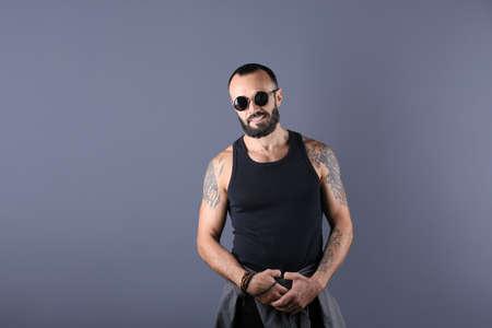 Portrait of handsome tattooed man on grey background