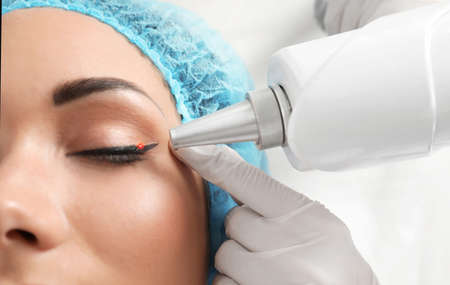 Woman undergoing laser tattoo removal procedure in salon, closeup Standard-Bild - 110691705