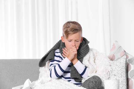 Garçon malade souffrant de toux sur canapé à la maison