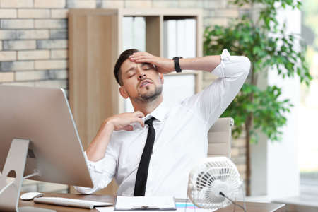 Businessman suffering from heat in front of small fan at workplace