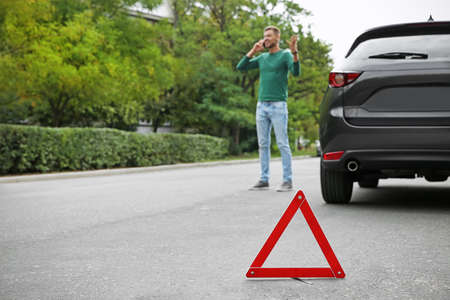 Emergency stop sign and man near broken car on background