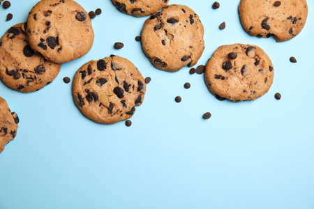 Delicious chocolate chip cookies on color background, flat lay. Space for text