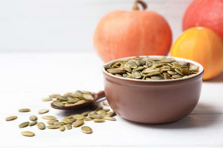 Shelled raw pumpkin seeds in dish on white table