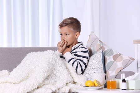 Ill boy suffering from cough on sofa at home Banque d'images