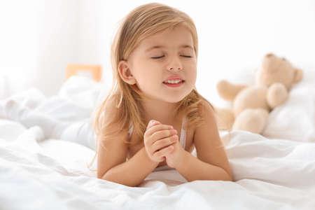 Niña rezando en la cama en casa Foto de archivo