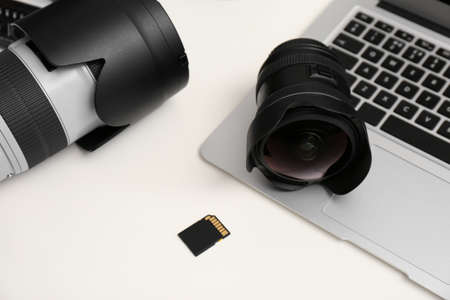 Laptop and professional photographer's equipment on white table