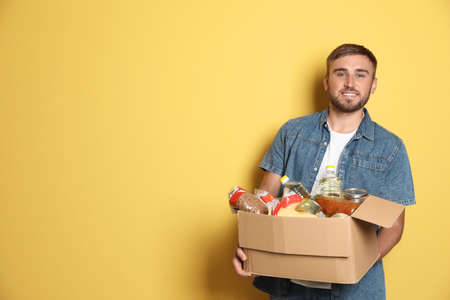 Young man holding box with donations on color background. Space for text