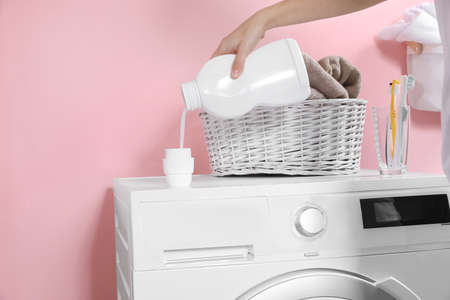 Woman pouring liquid detergent into cap on washing machine in laundry room, closeup