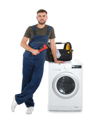 Plumber with wrench near washing machine on white background