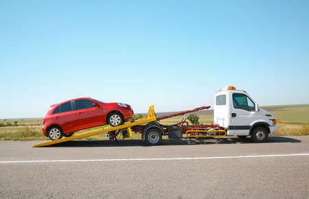 Carro attrezzi con automobile rotta sulla strada di campagna