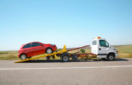 Tow truck with broken car on country road Imagens - 111556528