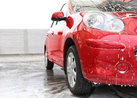 Rotes Auto mit Schaum bei Autowaschanlage. Platz für Text Standard-Bild