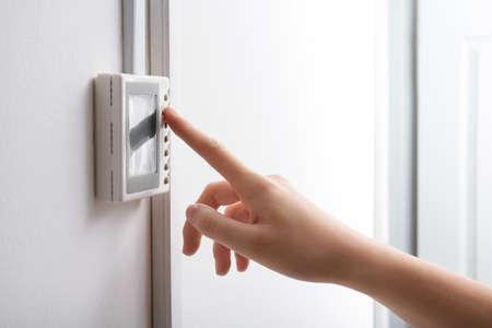 Mujer ajustando el termostato en la pared blanca, primer plano. Sistema de calefacción