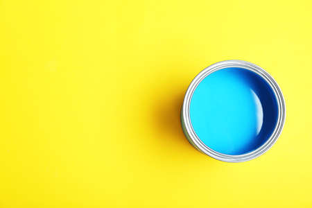 Paint can on yellow background, top view. Space for text