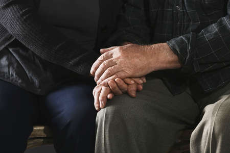 Poor elderly couple holding hands together, closeup
