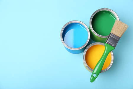 Flat lay composition with paint cans and brush on color background. Space for text
