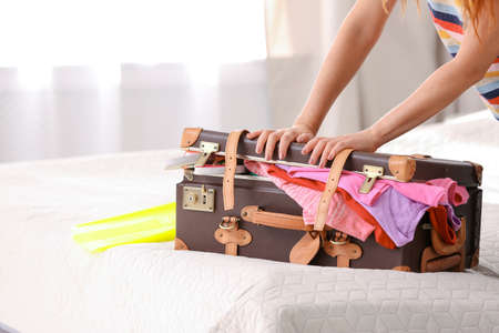 Woman packing suitcase for journey at home 免版税图像
