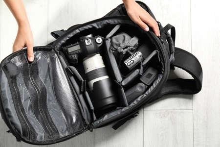 Mujer poniendo el equipo del fotógrafo profesional en la mochila en el piso, vista superior Foto de archivo