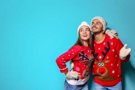 Young couple in Christmas sweaters and knitted hats on color background. Space for text
