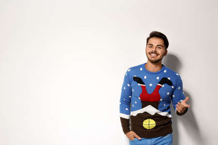 Young man in Christmas sweater on white background. Space for text Stok Fotoğraf