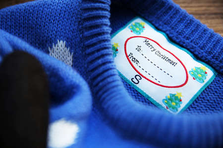 Christmas sweater with tag, closeup. Festive gift