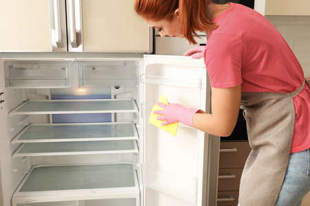 Woman in protective gloves cleaning refrigerator with rag indoors Фото со стока - 110846114