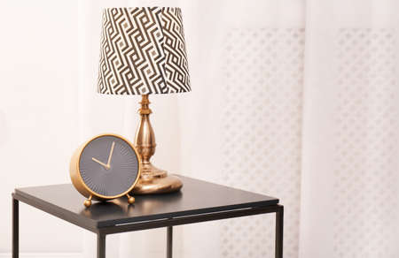 Analog clock and lamp on table indoors, space for text. Time of day