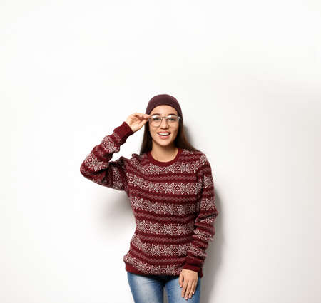 Young woman in warm sweater and hat on white background. Celebrating Christmas