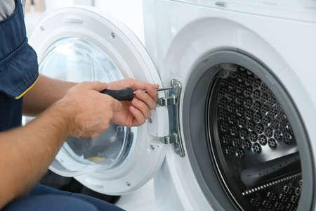 Giovane idraulico che ripara la lavatrice in bagno, primo piano Archivio Fotografico