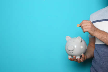 Man putting coin into piggy bank on color background, closeup with space for text