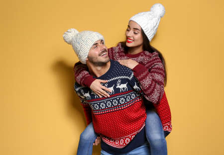 Young couple in warm sweaters and knitted hats on color background. Christmas celebration 写真素材