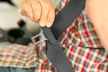 Male driver fastening safety belt in car, closeup Reklamní fotografie