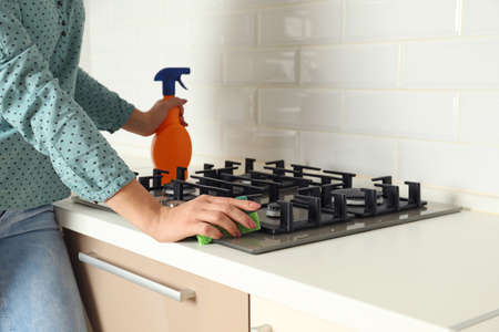 Woman cleaning gas stove with sponge in kitchen, closeup