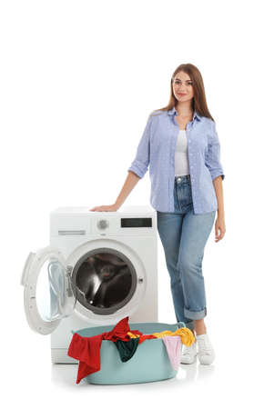 Young woman near washing machine and basket with laundry on white background Imagens