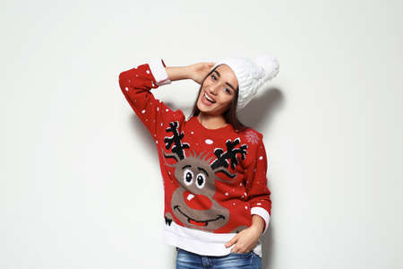 Young woman in Christmas sweater and knitted hat on white background