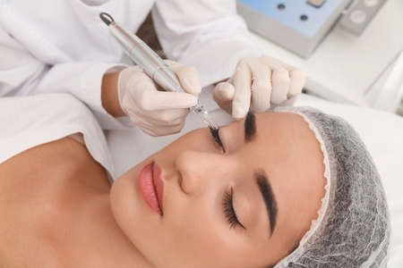 Young woman undergoing procedure of permanent eye makeup in tattoo salon, closeup 写真素材