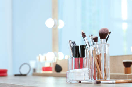 Organizer with cosmetic products for makeup on table near mirror. Space for text Stock Photo